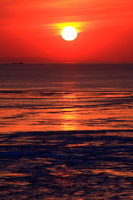 大潮潮動く夕日の海岸
