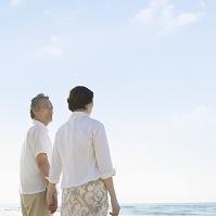 海辺で手を繋ぐ日本人シニア夫婦