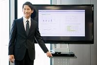 テレビの前に立つ日本人ビジネスマン