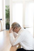 頭を抱えるシニアの日本人男性