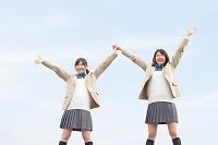 両手を上げる女子高校生