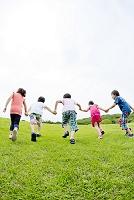 公園を手を繋いで走る小学生後ろ姿