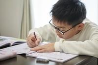 勉強する眼鏡の日本人の子供