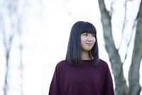 木立ちの中で微笑む日本人女性