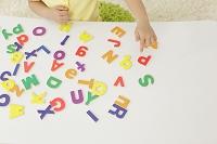 アルファベットのパズルで遊ぶ女の子の手