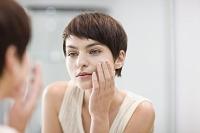 頬に保湿クリームを塗る外国人女性