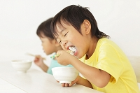 お茶碗を持ちごはんを食べる男の子と日本人の女の子