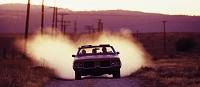 埃を舞い上げて走るクラシックカー