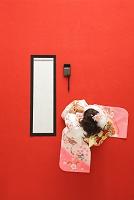 振り袖を着て書初めをする日本人の女の子