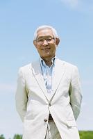 空と笑顔のシニアの日本人男性