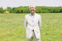 新緑と笑顔のシニアの日本人男性