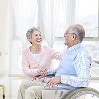 車椅子に座る男性と付き添う日本人女性