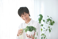 観葉植物に水やりする日本人男性