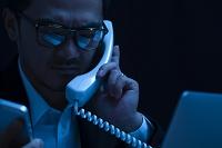 パソコンを見ながら電話をかける日本人男性