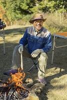 焚き火を起こすシニアの日本人男性