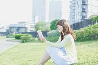 芝生の上で読書をする日本人女性