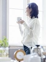 窓辺でコーヒーカップを持つ日本人女性