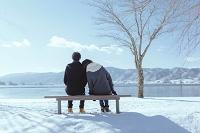 湖畔のベンチに座るカップルの後姿