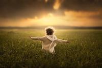 光の差す草原に立つ男の子