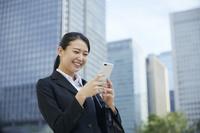 スマートフォンを見て笑う日本人ビジネスウーマン