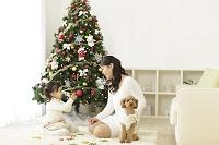 クリスマスツリーのあるリビングで遊ぶ親子と犬