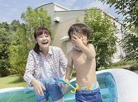 プールで水遊びする日本人親子