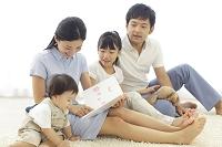 リビングで絵本を読む家族とペット