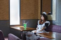 喫茶店にいるメイド服を着た日本人女性