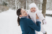 雪道で赤ちゃんを抱き上げる母親