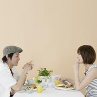 向かい合って食事をするカップル