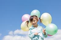 複数の風船を持っている日本人の女の子