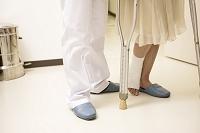 男性看護師に支えられる松葉杖女性の足下2