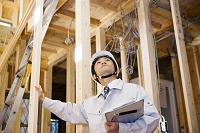 建築中の家の中をチェックする現場監督