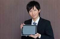 iPadを見せているビジネスマン