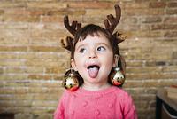 クリスマスオーナメントを耳に飾る子供