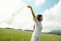 青空の下でショールを広げる若い日本人女性