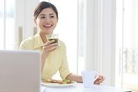 パソコンを見ながら朝食を食べる日本人女性