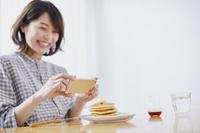 パンケーキを撮影する日本人女性