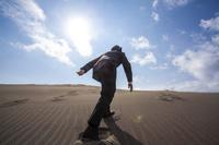 砂丘を上る日本人ビジネスマンの後ろ姿