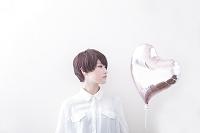 ハート型の風船を見つめる日本人女性