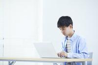 ノートパソコンを操作する男子中学生