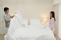 ベッドメイキングをする夫婦