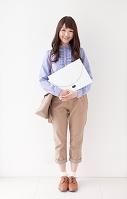 書類を抱えて立つ日本人女性
