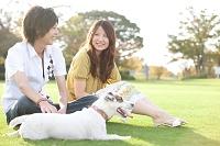 芝生に座っているカップルと犬