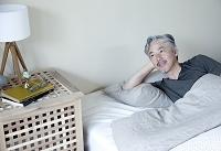 ベッドで横になるミドル日本人男性