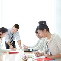 勉強している学生と外国人の先生