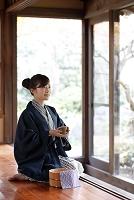 縁側でお茶を飲む日本人女性