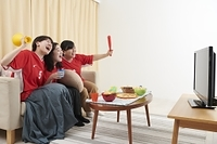 家でスポーツ観戦をする日本人女性
