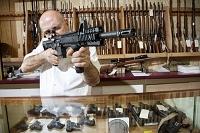 ガンショップでライフル銃を構える販売員