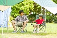 キャンプ場で椅子に座って談笑する父親と息子